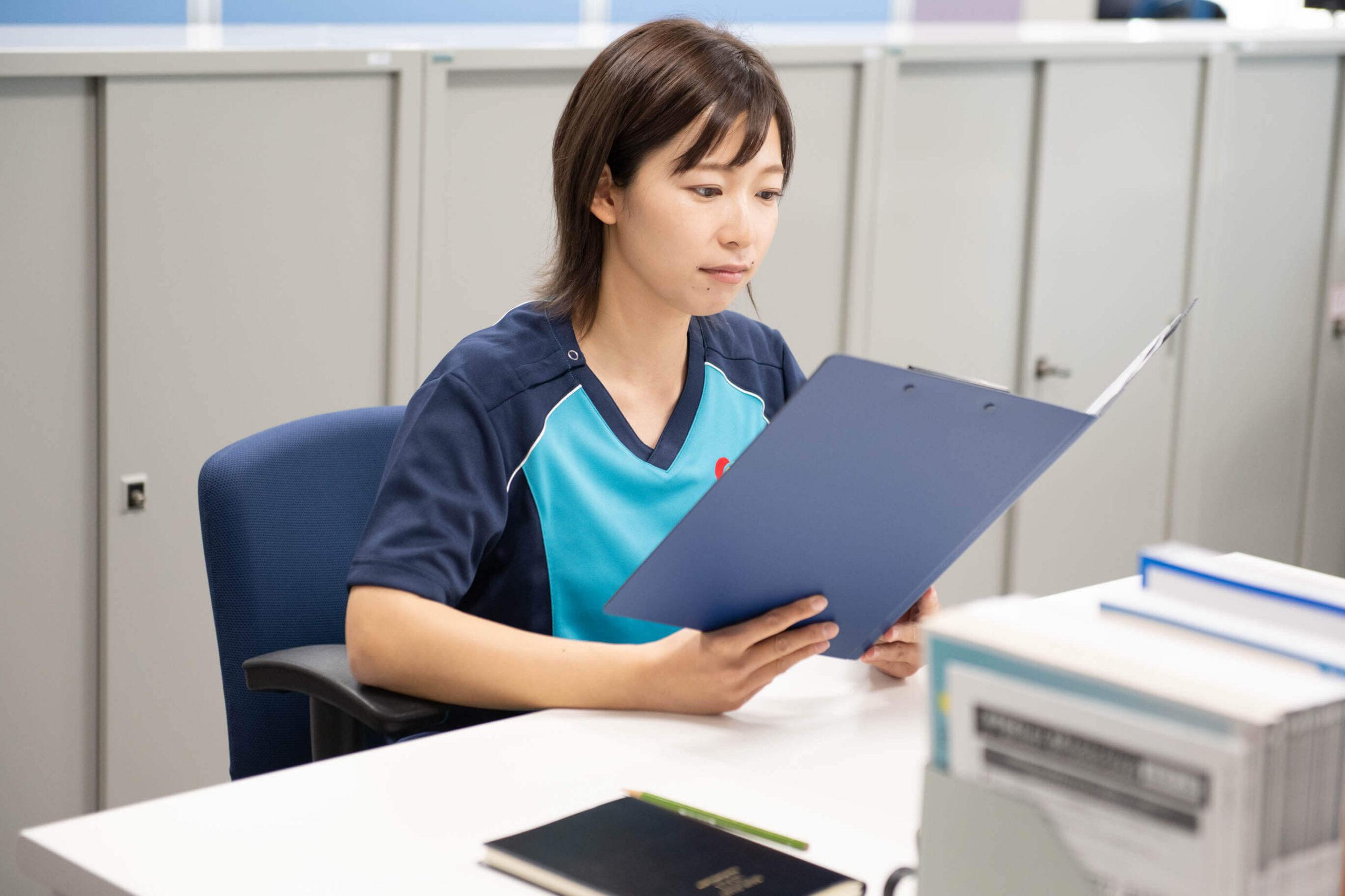 アサヒサンクリーンの女性社員がファイルに挟んである書類に目を通している写真