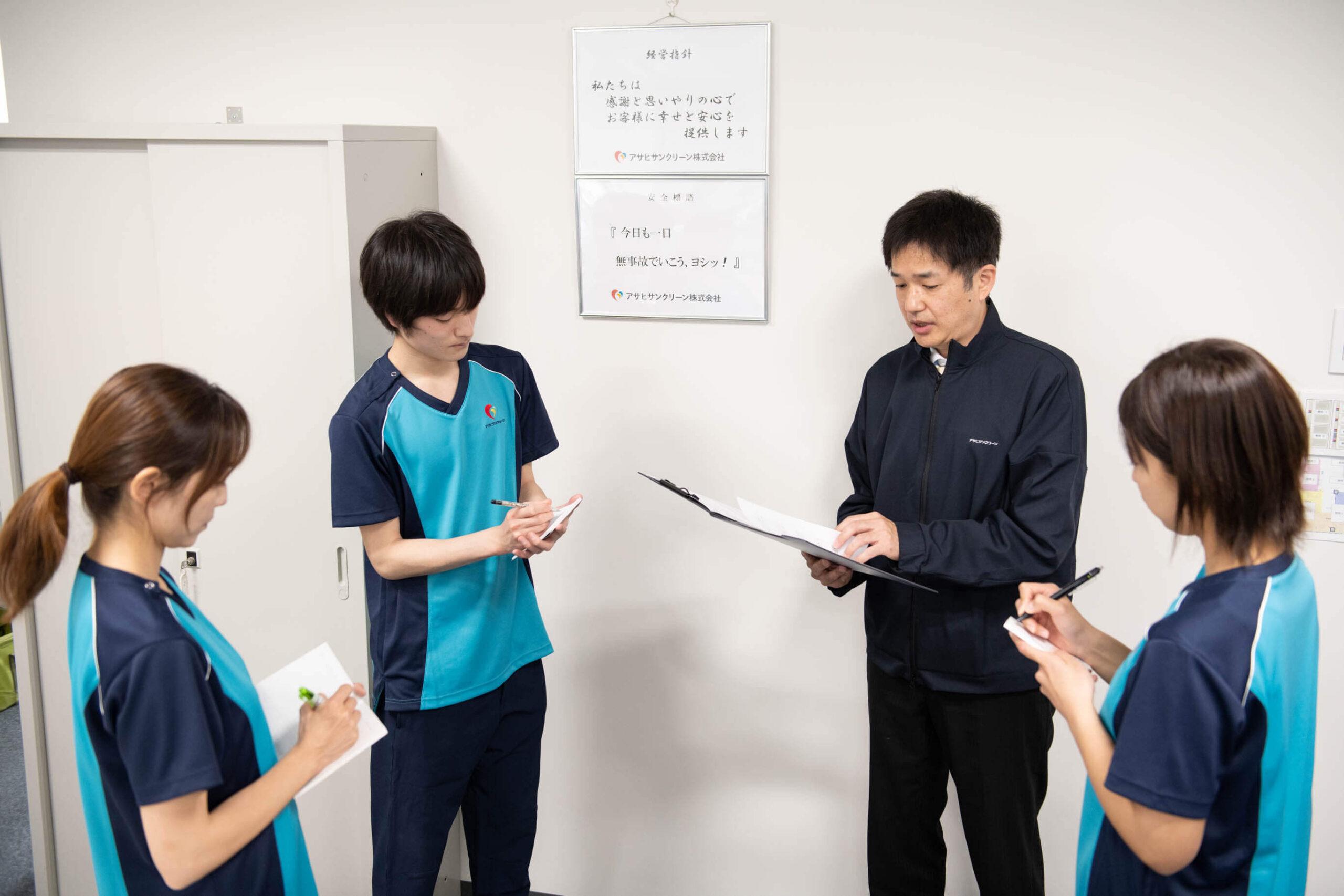 アサヒサンクリーンの社員4人が朝礼で紙を見ながら当日の訪問スケジュールを確認している写真