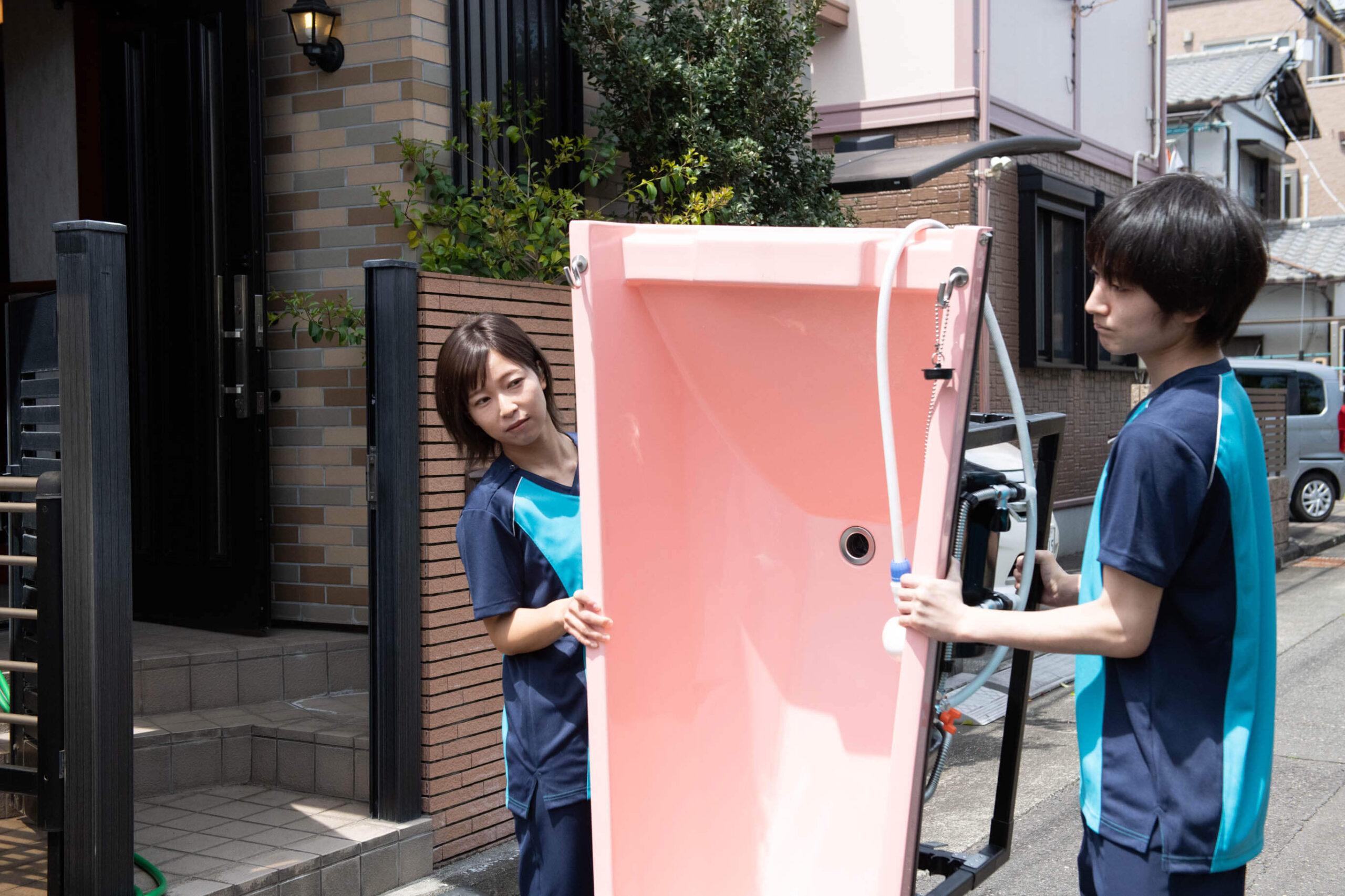 アサヒサンクリーンの女性社員と男性社員が浴槽を搬入している