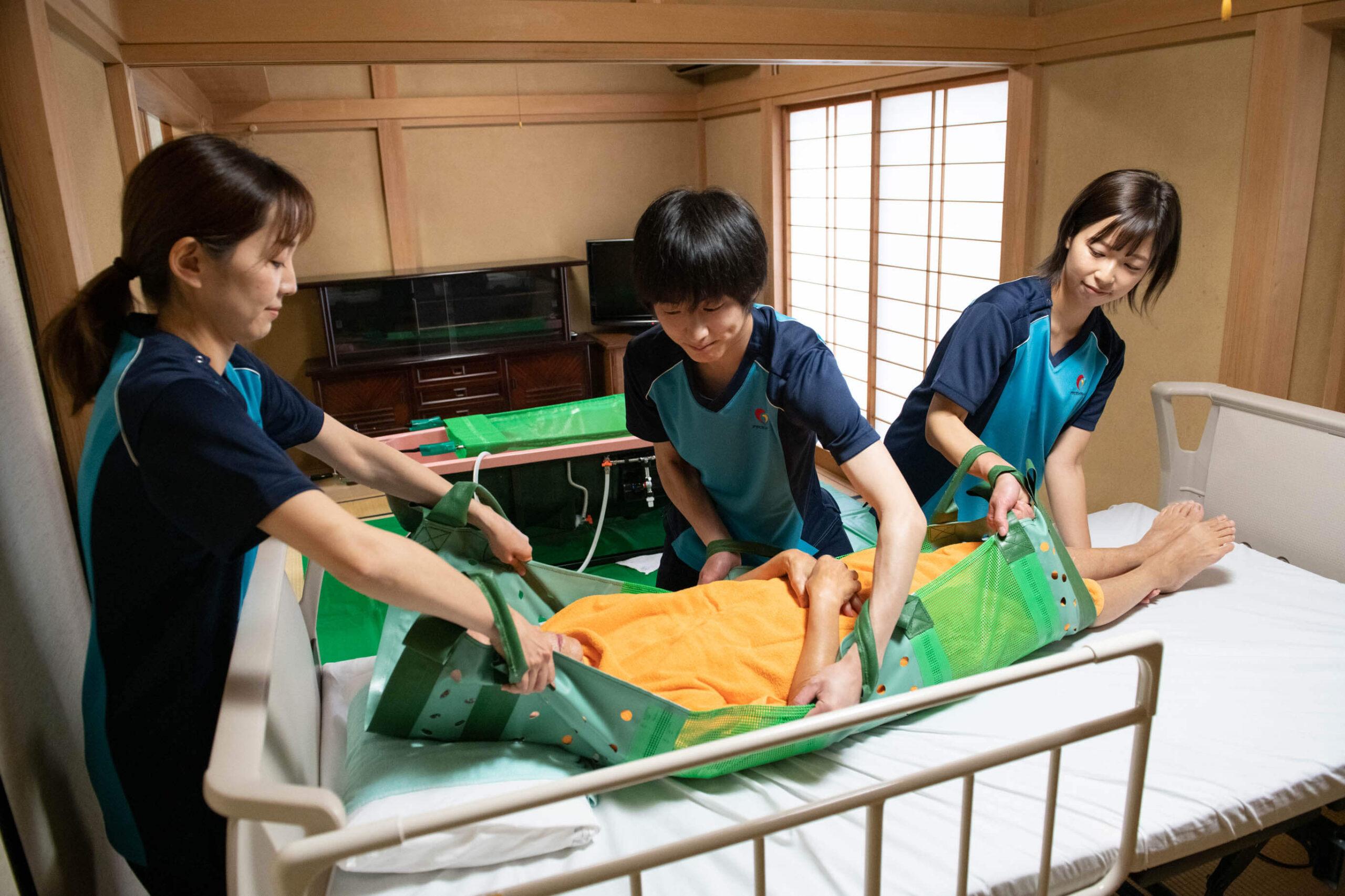 アサヒサンクリーンの女性社員2人と男性社員1人が要介護者をベットに移している写真